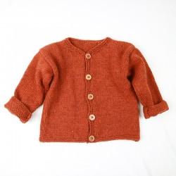 Look traditionnel pour ce cardigan bébé à boutons en bois tricoté à la main
